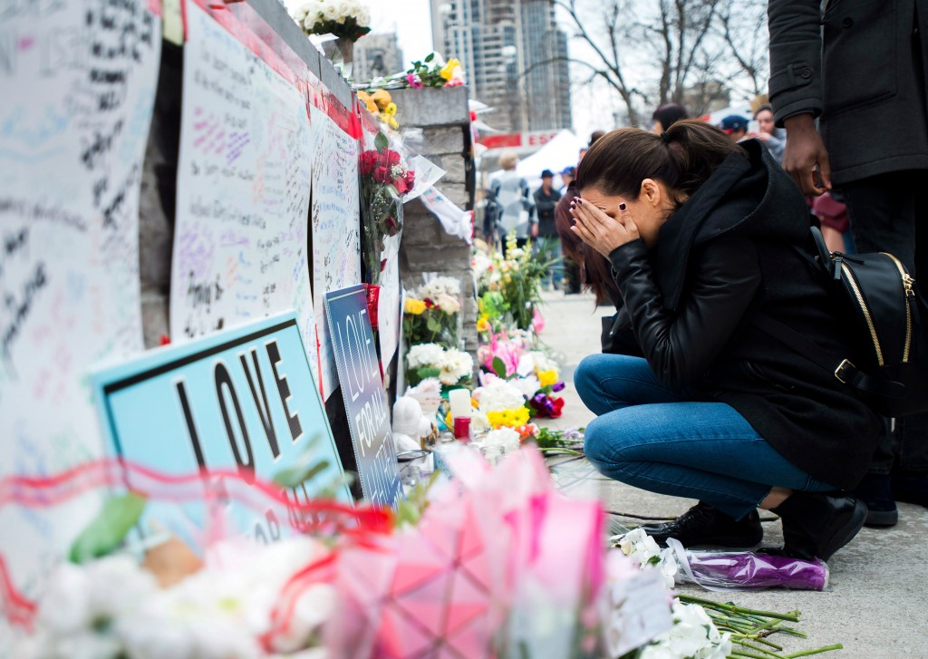 A women fights back tears at a memorial along Yonge Street, Tuesday, April 24, 2018, in Toronto, the day after a driver drove a van down sidewalks, st...