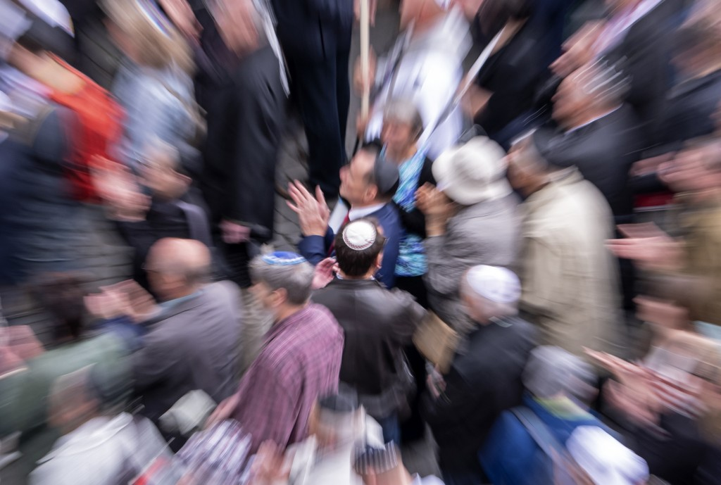 In this zoomed and long time exposure picture people of different faiths wear the Jewish kippah during a demonstration against antisemitism in Germany...