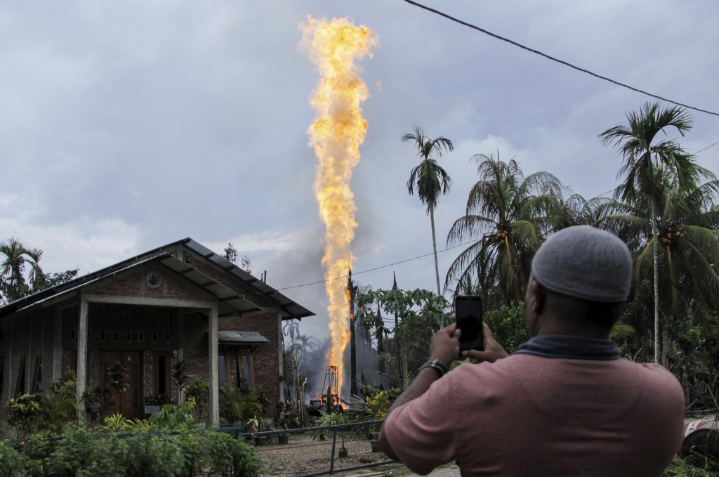 In this Wednesday, April 25, 2018, file photo, a man uses his mobile phone to take pictures of a burning oil well after it was caught fire in Pasir Pu...