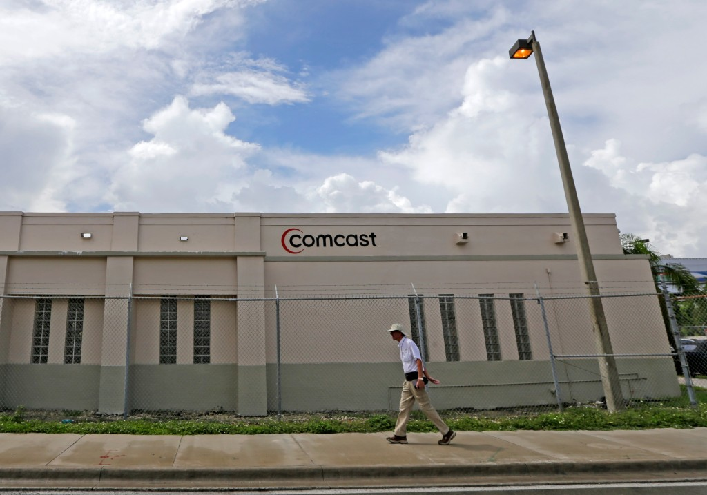 FILE- In this Oct. 12, 2017, file photo a pedestrian walks by a Comcast Service Center, in Miami. Comcast Corp. reports earnings Wednesday, April 25, ...