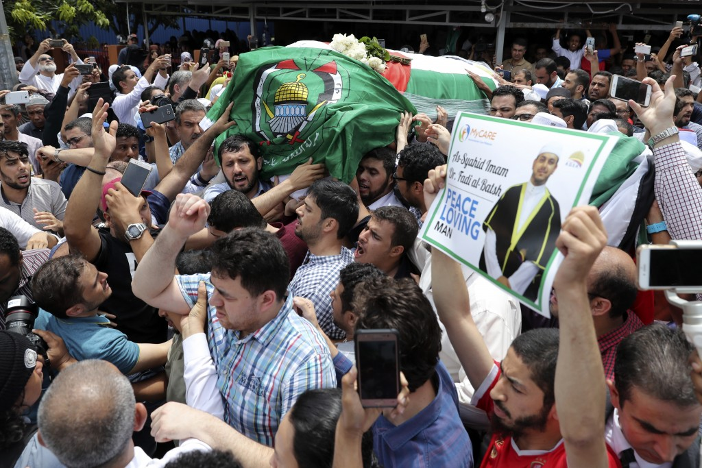 In this Wednesday, April 25, 2018, file photo, the coffin of Palestinian Fadi al-Batsh is carried out of a mosque after a prayer in Selayang, on the o...