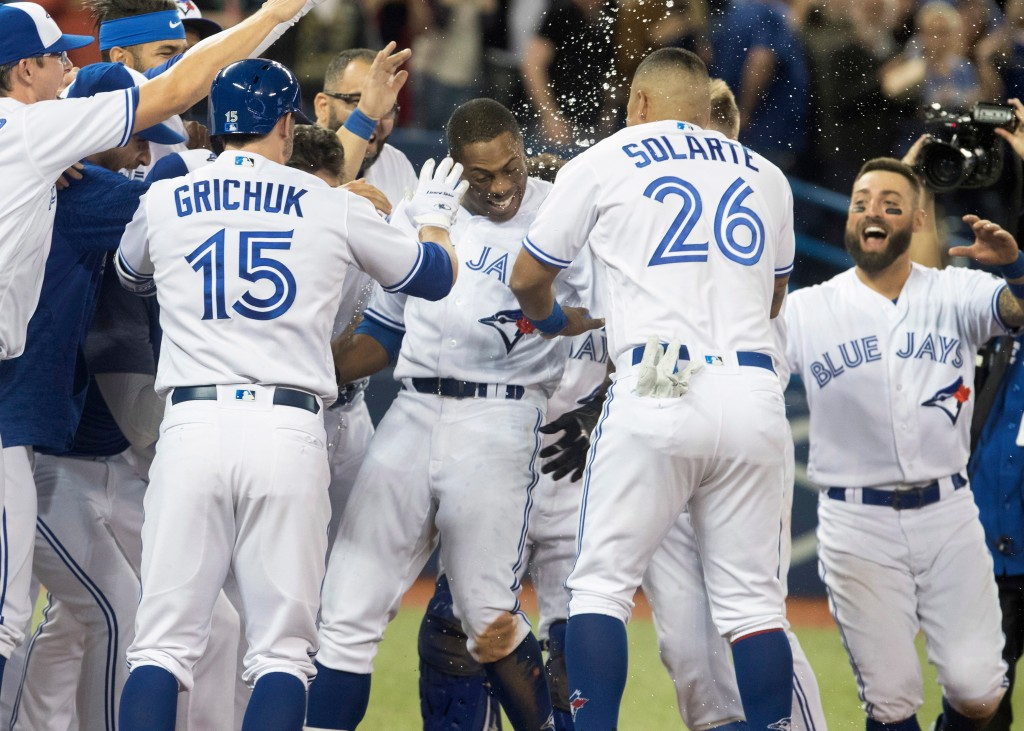 Toronto Blue Jays' Curtis Granderson, center, is welcomed by teammates after he hit a walk-off home run against the Boston Red Sox during the 10th inn...
