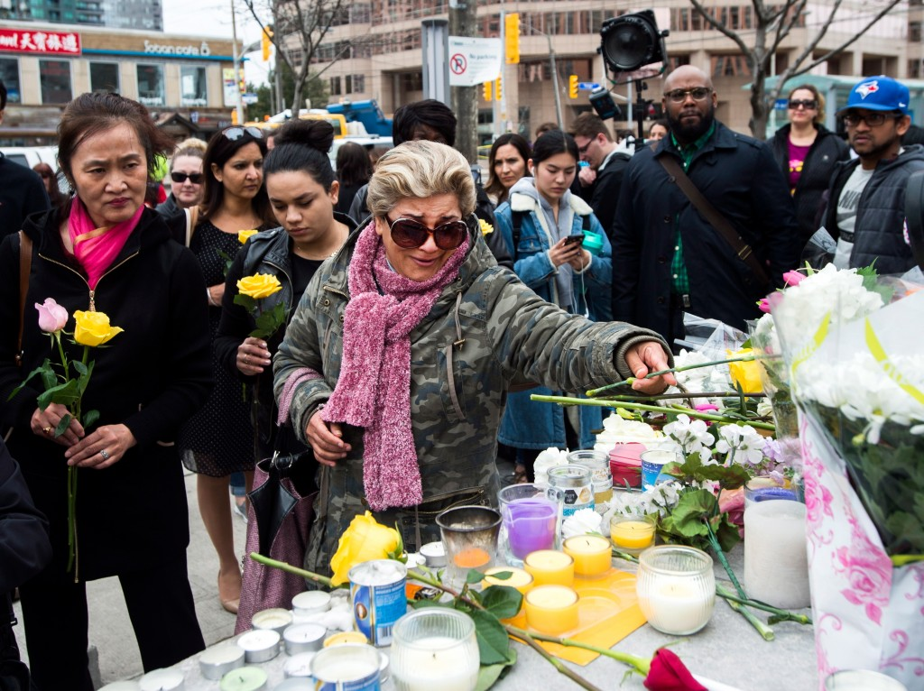 Ozra Kenari, center, places flowers as she cries at a memorial for the victims along Yonge Street the day after a driver drove a van down sidewalks, s...