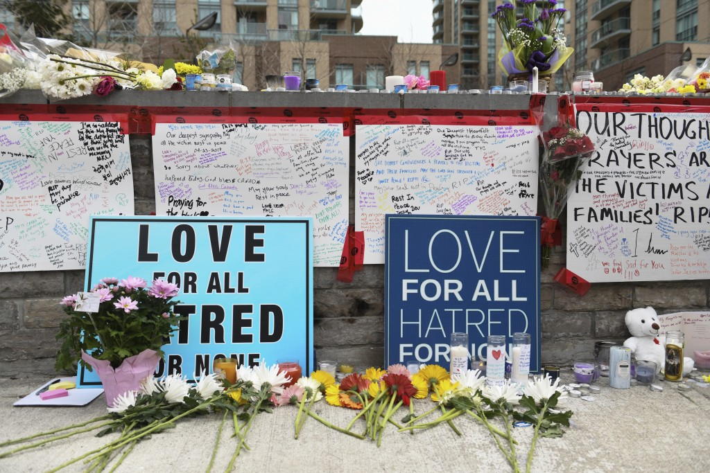Flowers and signs fill a memorial along Yonge Street Tuesday, April 24, 2018, in Toronto, the day after a driver drove a van down sidewalks, striking ...