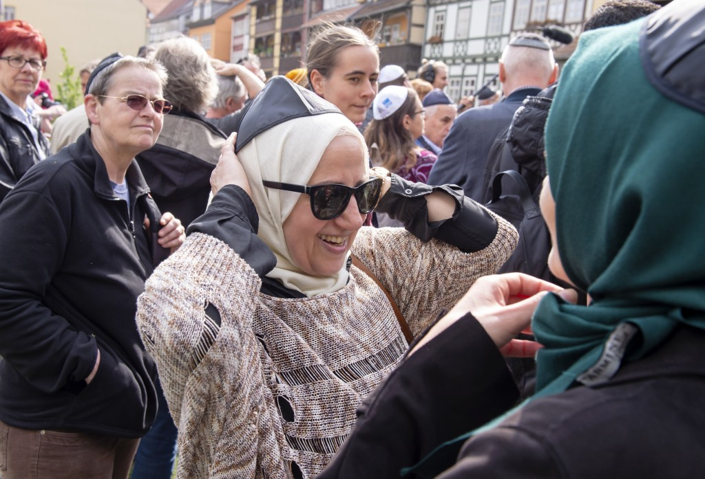 Muslim woman Samar Allaham, center, fixes the Jewish kippah  on her head besides the Muslim woman Iman Jamous, right, during a demonstration against a...