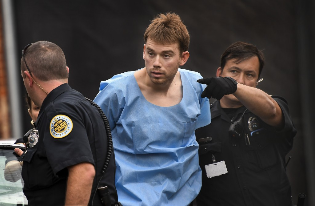 In this Monday, April 23, 2018 photo, Travis Reinking, suspected of killing four people in a late-night shooting at a Waffle House restaurant, is esco...