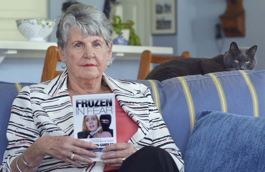 In this March 1, 2018, photo, rape survivor Jane Carson-Sandler, of Sun City Hilton Head, S.C. poses for a photo holding a copy of her book about the ...