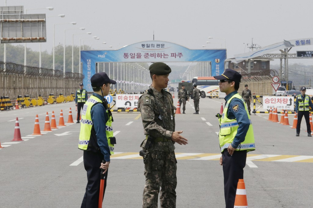 A South Korean army soldier, center, talks with police officers as they stand guard at Unification Bridge, which leads to Panmunjom in Paju, South Kor...