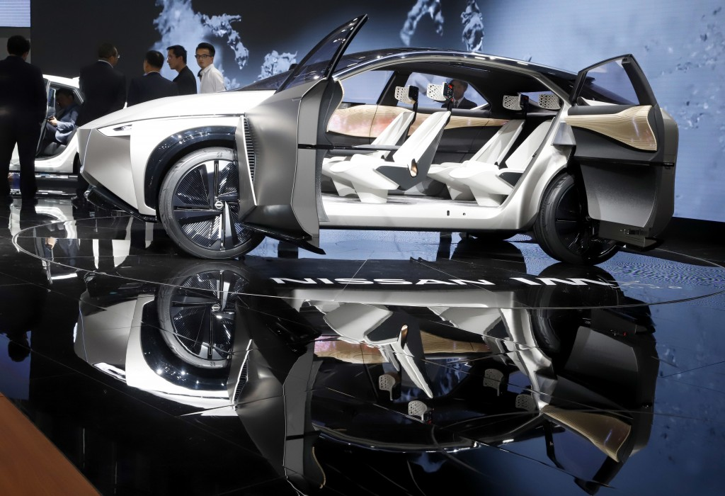 In this Thursday, April 26, 2018, file photo, visitors stand near the Nissan IMX concept car during Auto China 2018 in Beijing. Auto China 2018, the i...