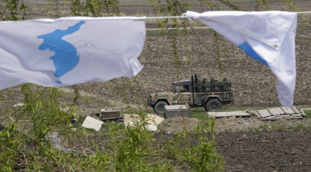 A South Korean military vehicle passes by unification flags near Unification Bridge, which leads to the Panmunjom in Paju, South Korea, Thursday, Apri...