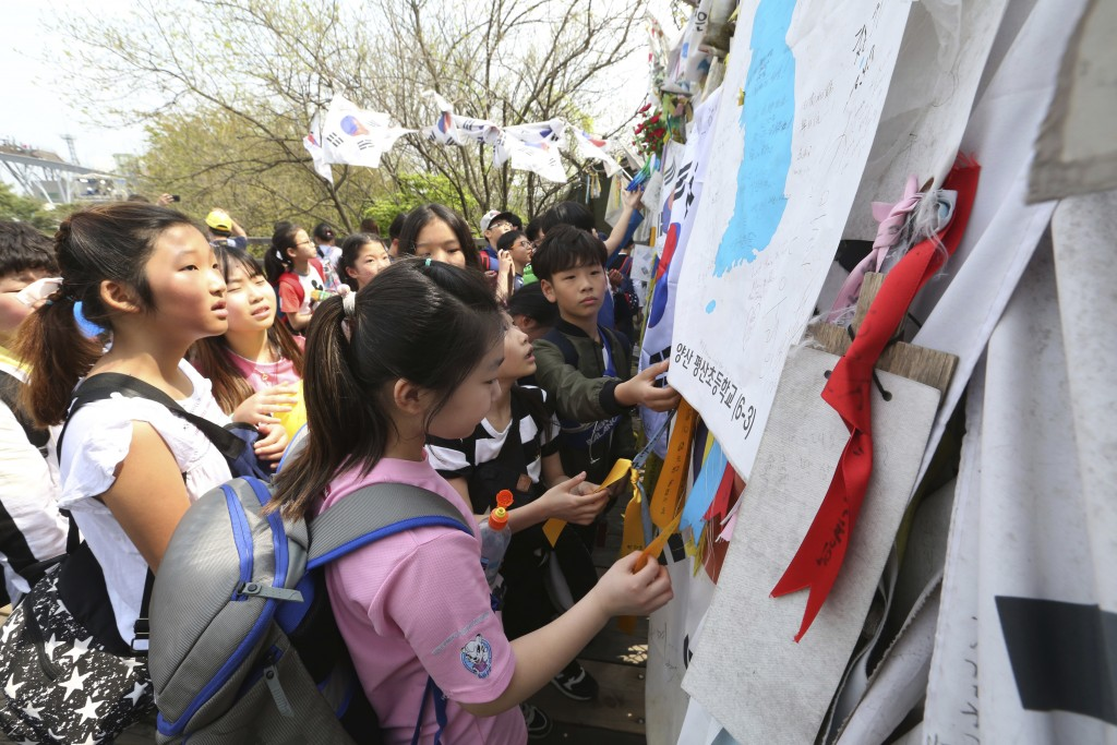 Elementary school students read banners placed on a barbed wire fence with messages wishing for the reunification of the two Koreas at the Imjingak Pa...