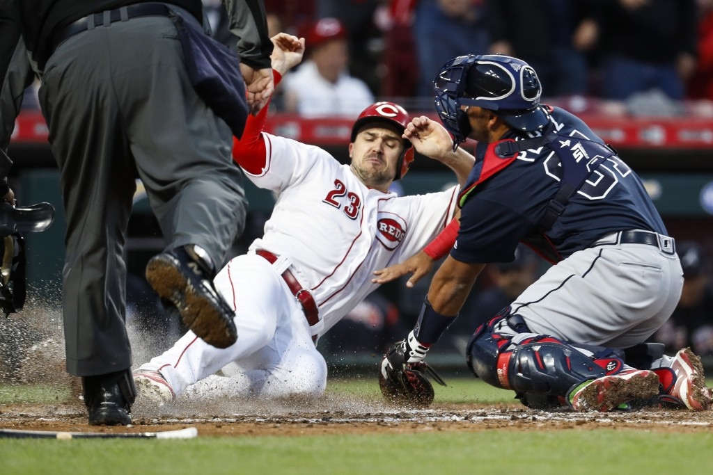 Cincinnati Reds' Adam Duvall (23) scores against Atlanta Braves catcher Carlos Perez, right, during the fifth inning of a baseball game Wednesday, Apr...