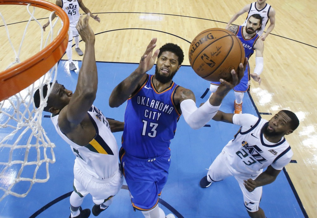 Oklahoma City Thunder forward Paul George (13) goes up for a shot between Utah Jazz center Ekpe Udoh, left, and forward Royce O'Neale (23) during the ...