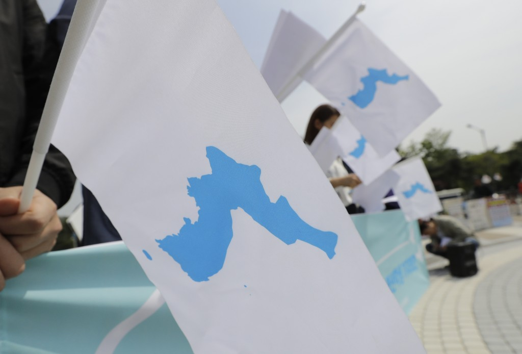 South Koreans hold unification flags to welcome the planned summit between South Korean President Moon Jae-in and North Korean leader Kim Jong Un near...
