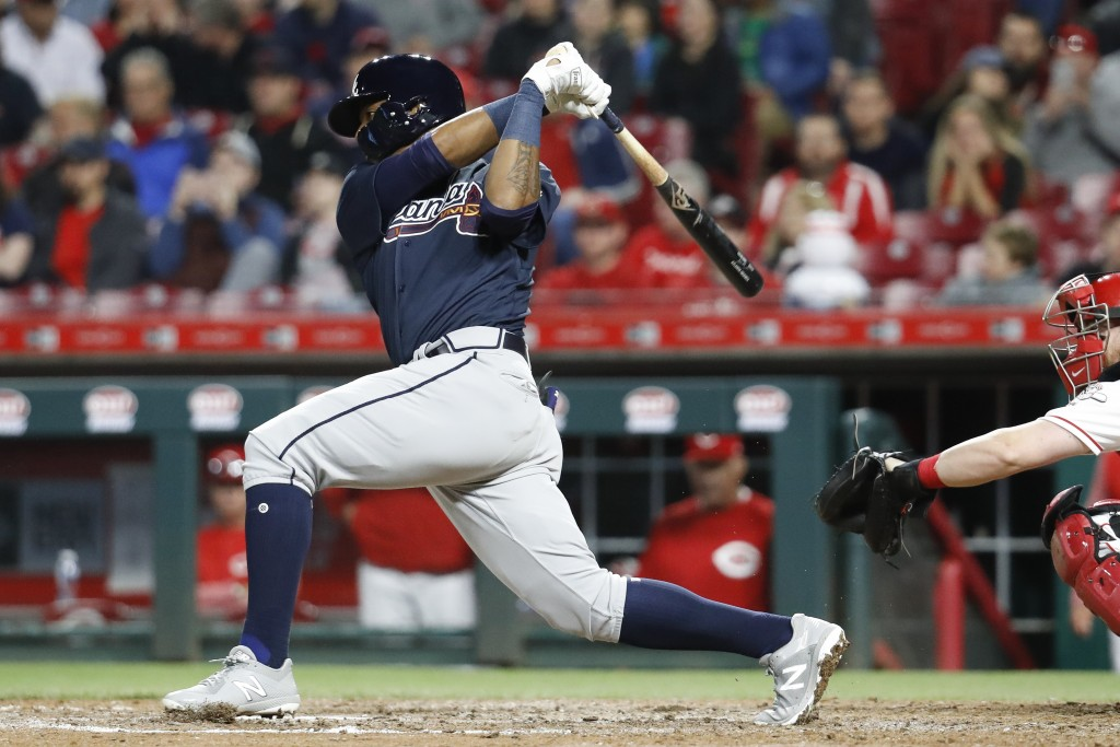 Atlanta Braves' Ronald Acuna Jr. follows through on a single off Cincinnati Reds relief pitcher Kevin Shackelford during the eighth inning of a baseba...
