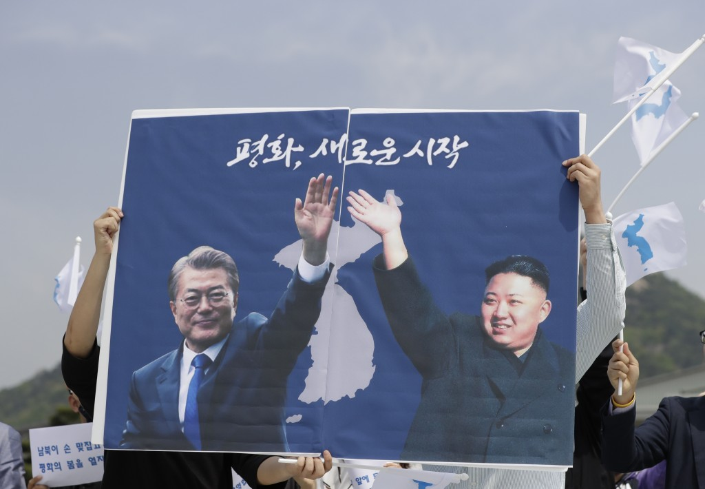 South Koreans hold a banner showing the pictures of South Korean President Moon Jae-in, left, and North Korean leader Kim Jong Un to welcome the plann...