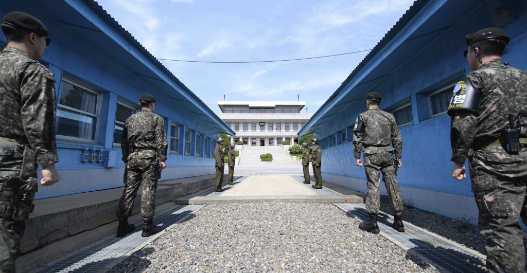 Four North Korean soldiers, center far, and four South Korean soldiers, right and left, stand at the border village of Panmunjom in the Demilitarized ...