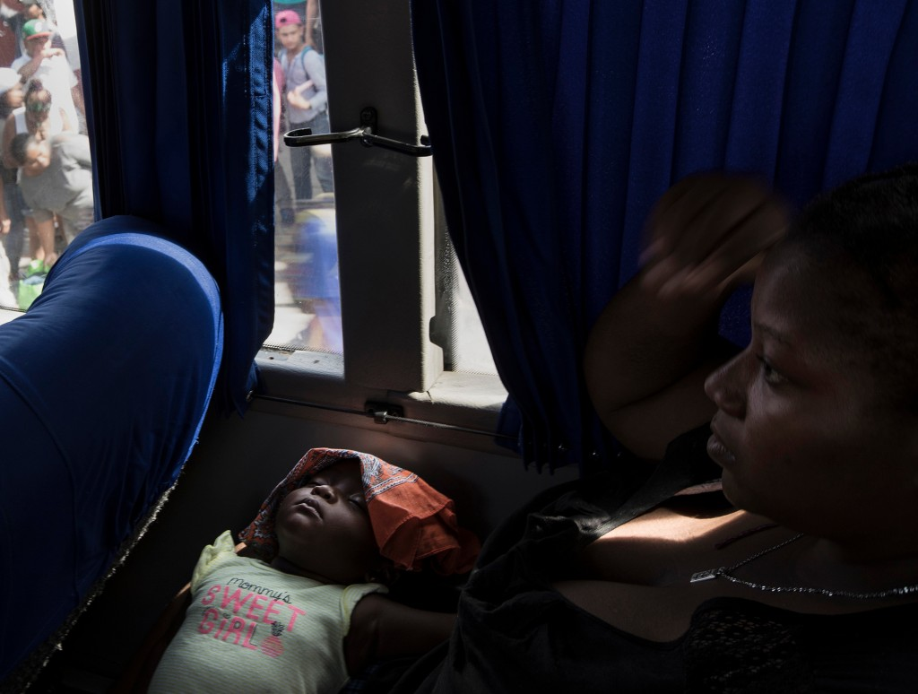 A woman and child, who are part of a caravan of Central American asylum-seekers, wait on a bus in Mexicali, Mexico, Thursday, April 26, 2018, that wil...
