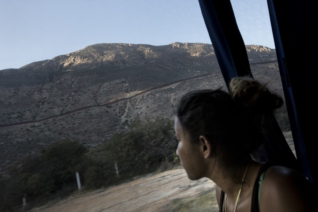 A Central American migrant looks out toward the border with the U.S., between Mexicali and Tijuana, as she rides by bus with a caravan of migrants to ...