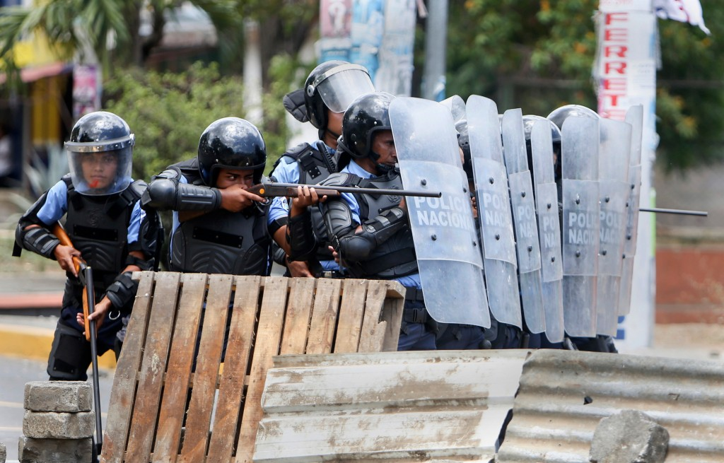 In this April 20, 2018 photo, a Nicaraguan police officer aims his weapon at protesting students during a third day of violent clashes in Managua, Nic...