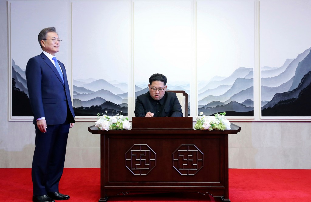 North Korean leader Kim Jong Un signs a guest book next to South Korean President Moon Jae-in, left, inside the Peace House at at the border village o...