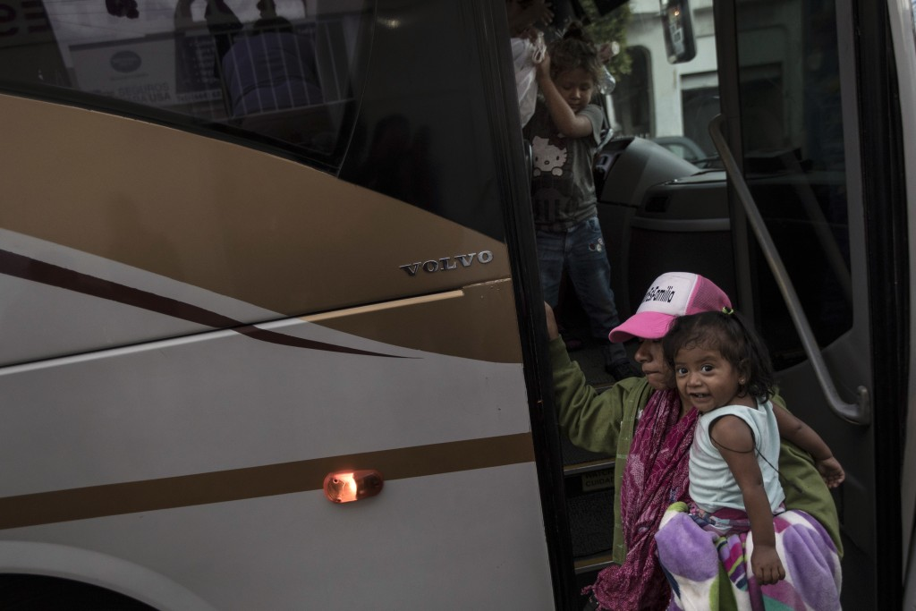 A Central American migrant and her children who are traveling with a caravan, arrive by bus to Tijuana, Mexico, Thursday, April 26, 2018. Caravans hav...
