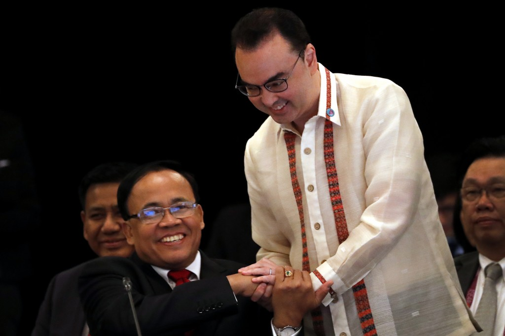 Philippine's Secretary of Foreign Affairs Alan Peter Cayetano, right, shakes hands with Myanmar's Union Minister for International Cooperation U Kyaw ...