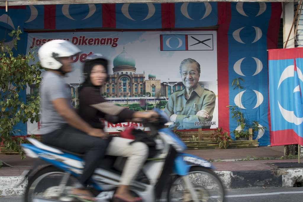 A motorcycle passes by an election poster of former Malaysian strongman Mahathir Mohamad  in downtown Langkawi, Malaysia, Friday, April 27, 2018. Mala...