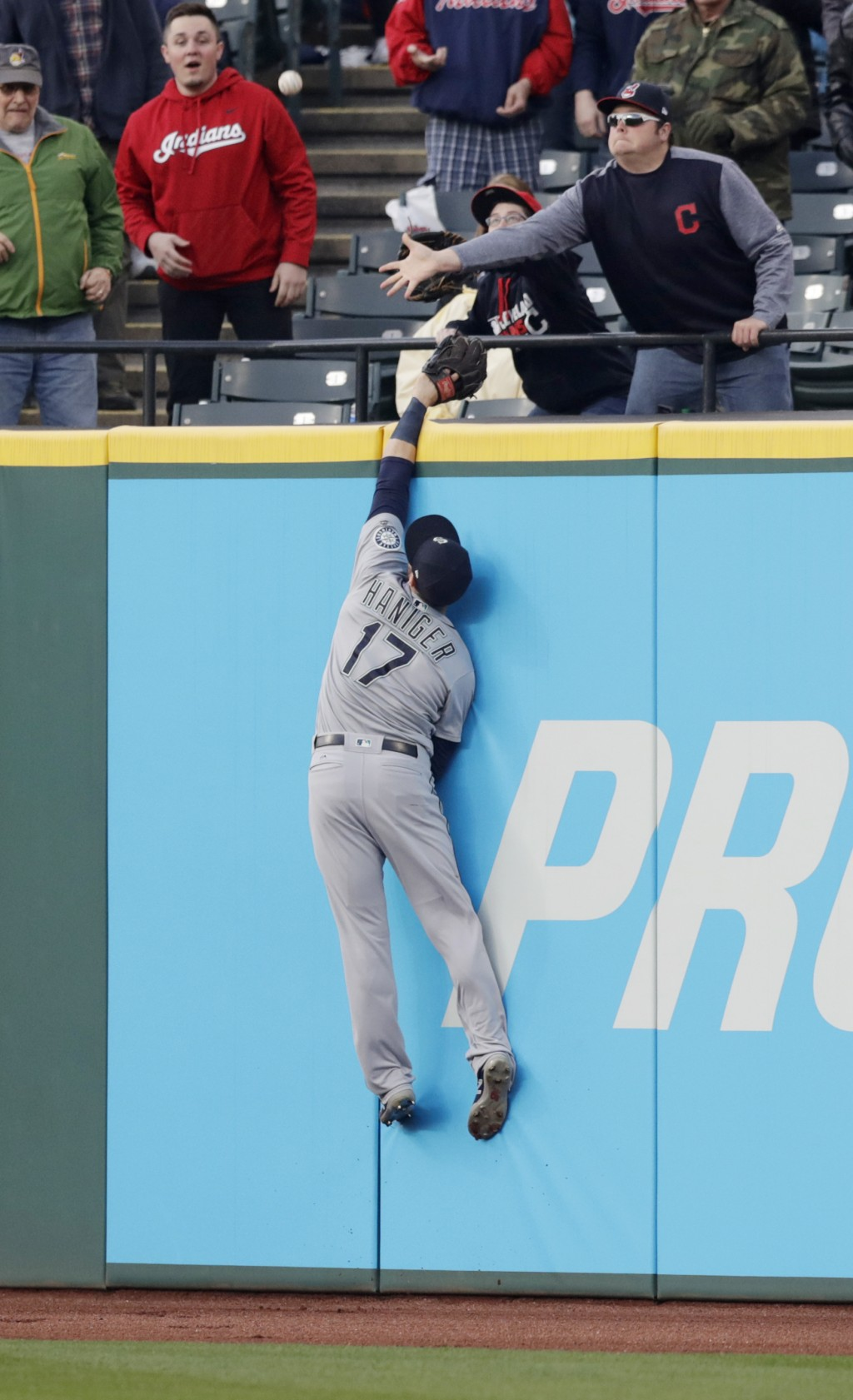 Seattle Mariners' Mitch Haniger jumps but can't reach a two-run home run by Cleveland Indians' Yonder Alonso during the sixth inning of a baseball gam...