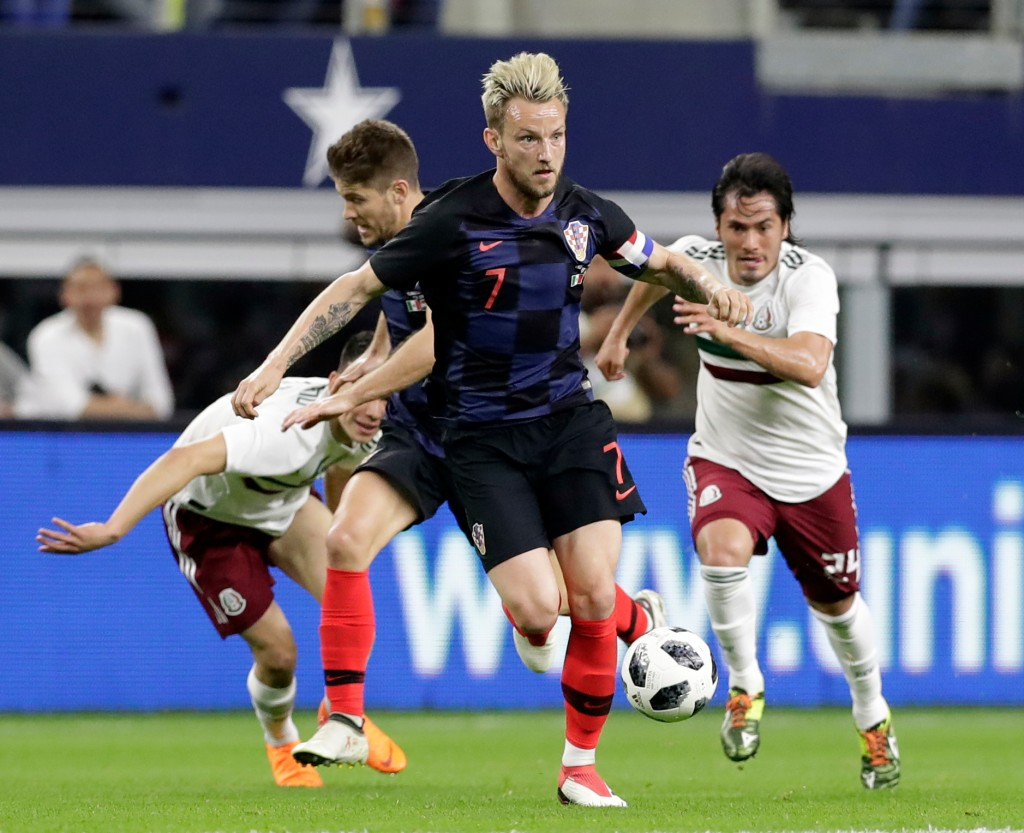 In this Photo taken on Tuesday, March 27, 2018, Croatia midfielder Ivan Rakitic, foreground, leads an attack as Mexico midfielder Jorge Hernandez, rig...