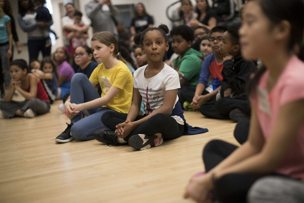 In this March 3, 2018 photo, young dance students watch a performance during the National Dance Institute alumni homecoming celebration at NDI headqua...