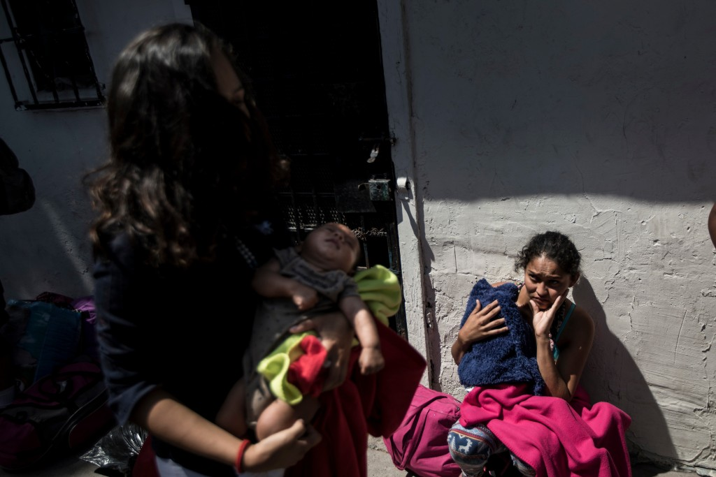 In this April 25, 2018 photo, Central American mothers and children who are traveling with a caravan of migrants, wait to figure out their night's acc...