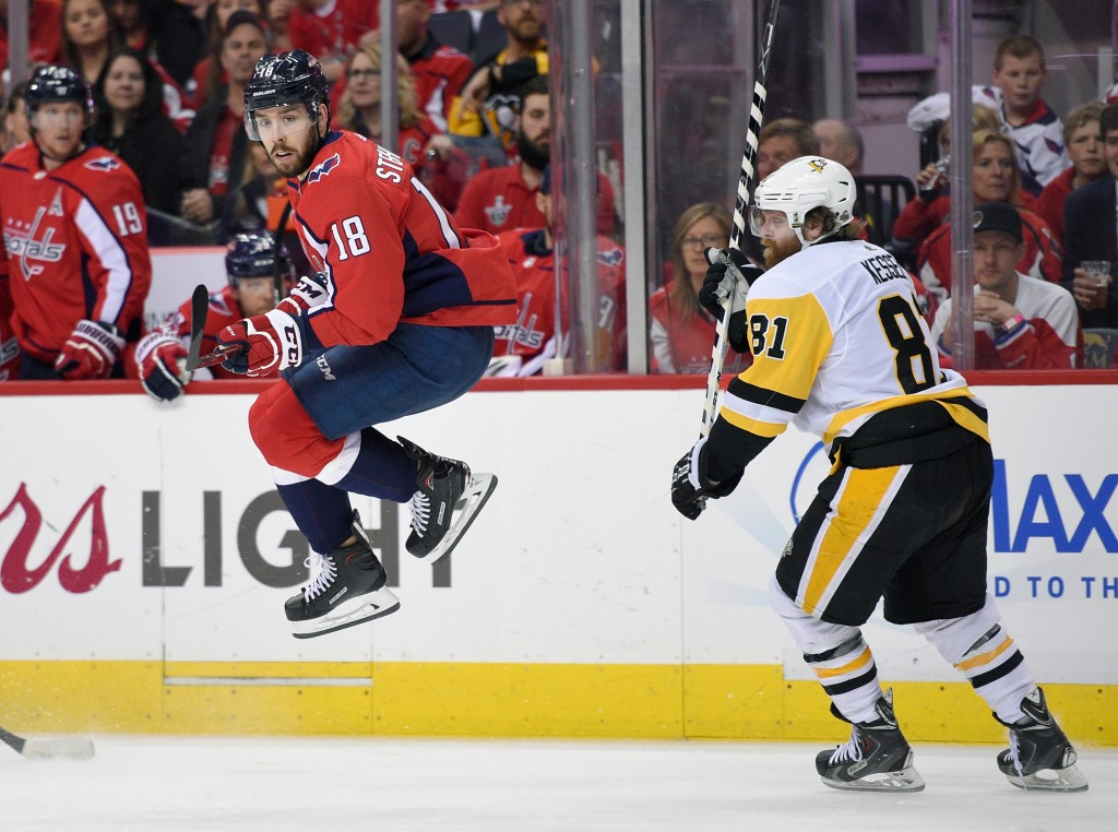 Washington Capitals center Chandler Stephenson (18) leaps next to Pittsburgh Penguins right wing Phil Kessel (81) during the second period in Game 1 o...