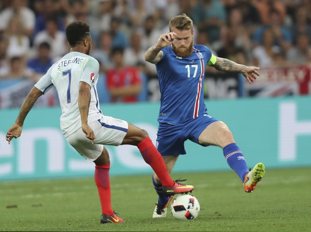 FILE - In this Monday, June 27, 2016 file photo, England's Raheem Sterling, left, fights for the ball with Iceland's Aron Gunnarsson during the Euro 2...