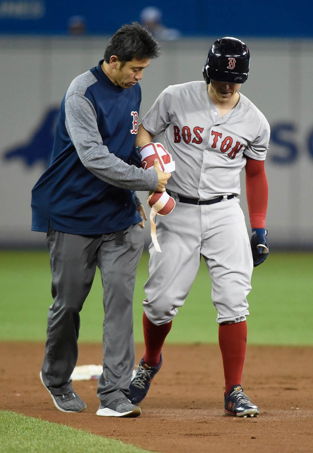 Boston Red Sox second baseman Brock Holt leaves with an injury during the third inning of the team's baseball game against the Toronto Blue Jays in To...