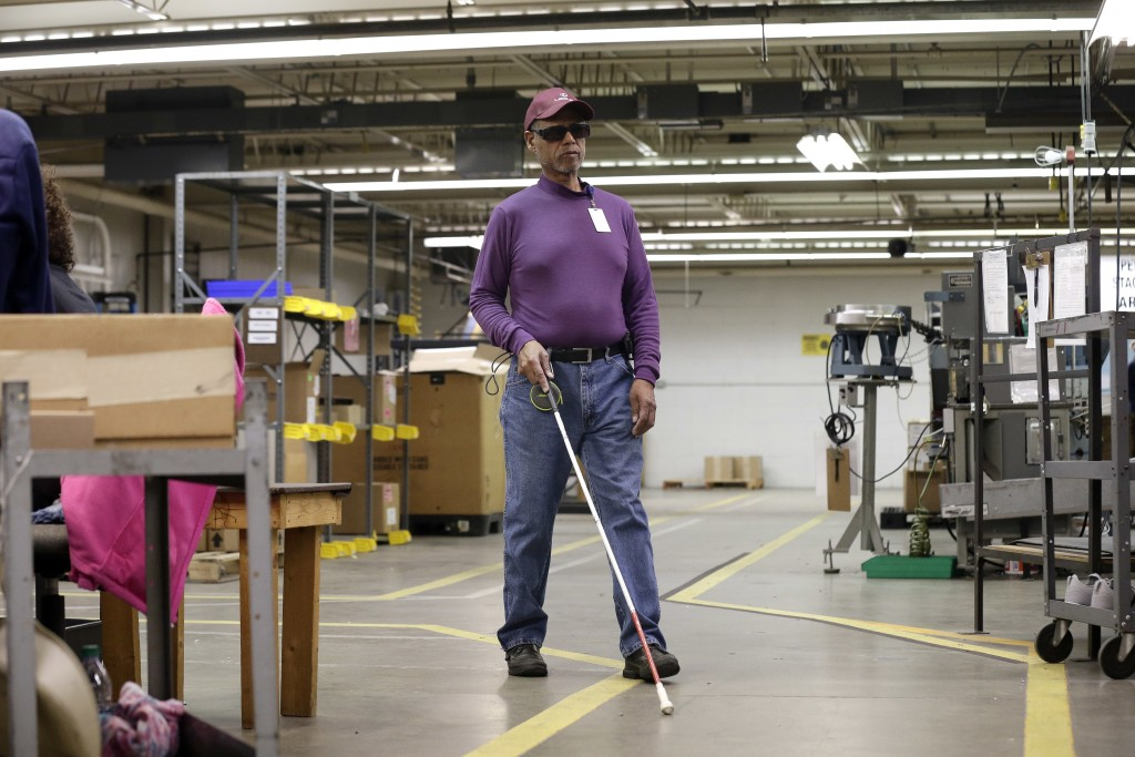 In this Monday, April 16, 2018, photo, employee Christopher Alexander makes his way through the SKILCRAFT pen assembly area at the Industries of the B...