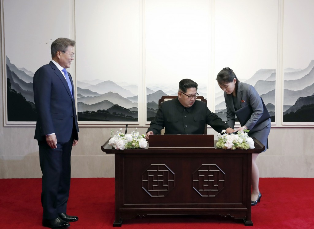 North Korean leader Kim Jong Un, center, receives a pen  from his sister Kim Yo Jong, right, to sign a guest book as South Korean President Moon Jae-i...