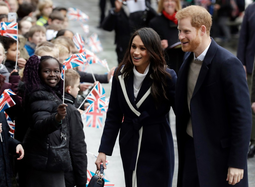 FILE - In this Thursday, March 8, 2018 file photo, Britain's Prince Harry and his fiance Meghan Markle are greeted by flag waving school children as t...