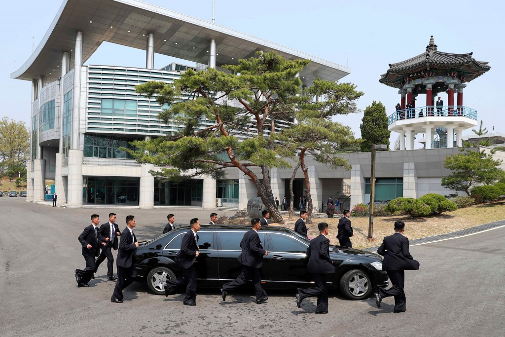 North Korean security persons run by a car carrying North Korean leader Kim Jong Un return to the North side for a lunch break after a morning session...