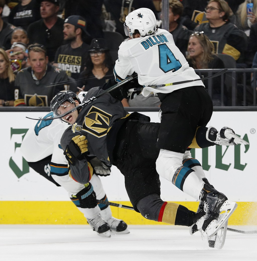 San Jose Sharks defenseman Brenden Dillon (4) checks Vegas Golden Knights left wing David Perron during the second period of Game 1 of an NHL hockey s...