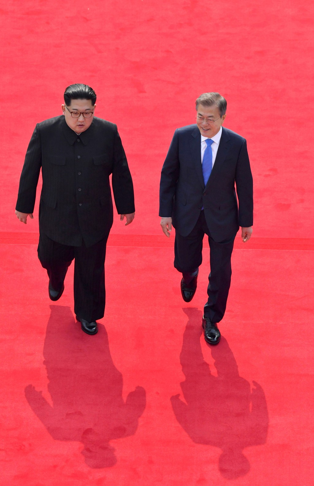 North Korean leader Kim Jong Un, left, and South Korean President Moon Jae-in walk toward the Peace House for their meeting at the border village of P...
