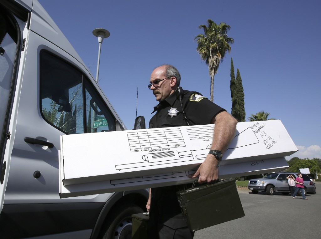 John Lopes, a crime scene investigator for the Sacramento Sheriff's office, carries boxes of evidence taken from the home of murder suspect Joseph DeA...