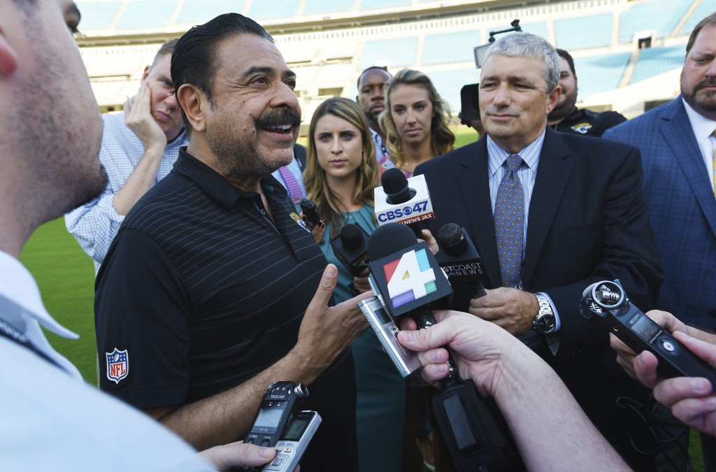 Jacksonville Jaguars owner Shad Khan, left, fields questions from the media on his interest in buying Wembley Stadium in London ahead of the Uniform L...