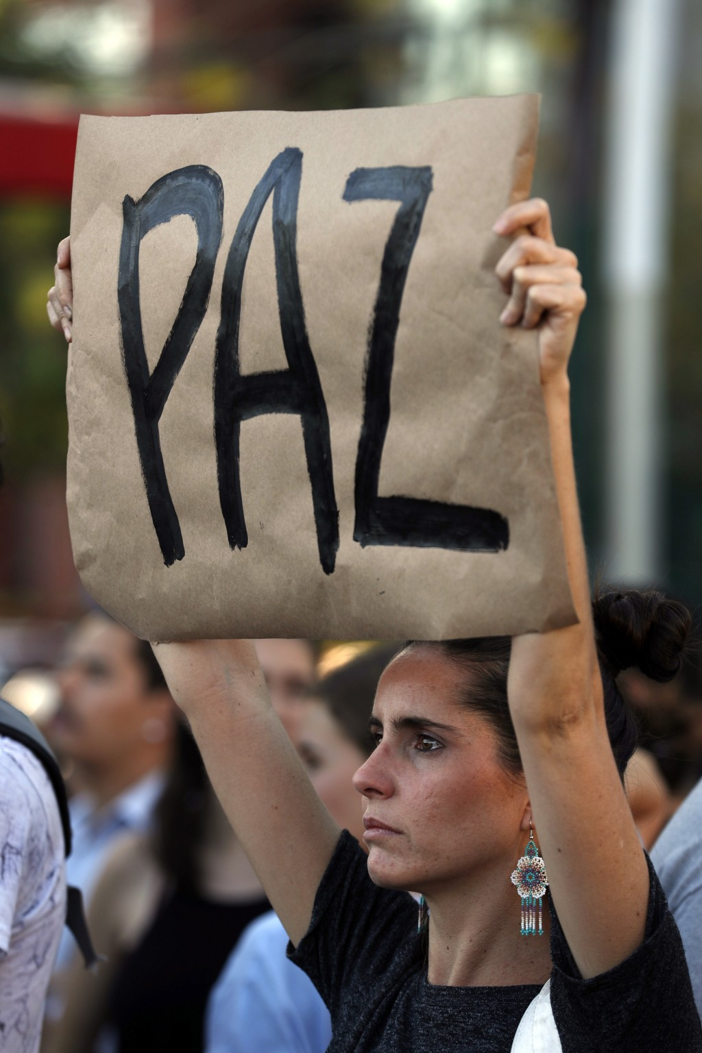 """A woman holds up a sign that says in Spanish """"Peace"""" during a protest against the murder of three film students who have become emblematic of Mexico's..."""