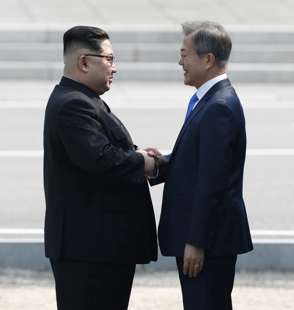 North Korean leader Kim Jong Un, left, shakes hands with South Korean President Moon Jae-in at the border village of Panmunjom in the Demilitarized Zo...