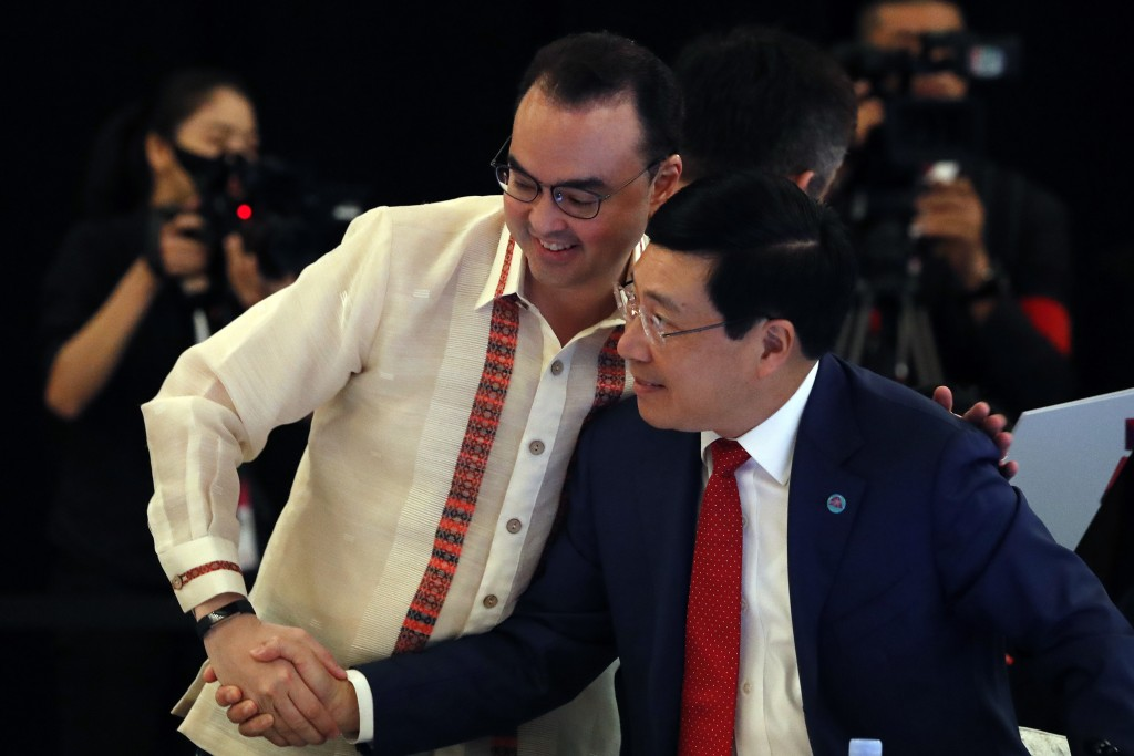 Philippine's Secretary of Foreign Affairs Alan Peter Cayetano, left, shakes hands Vietnam's Deputy Prime Minister Pham Binh Minh, ahead of the ASEAN F...