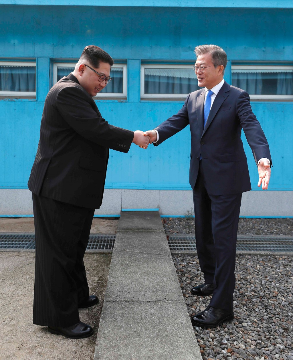 North Korean leader Kim Jong Un, left, shakes hands with South Korean President Moon Jae-in over the military demarcation line at the border village o...