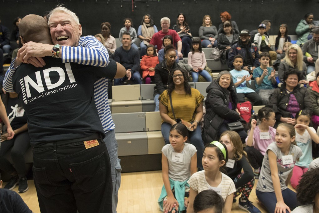 In this Saturday, March 3, 2018 photo, dancer, choreographer Jacques d'Amboise, second left, hugs a former student during the National Dance Institute...