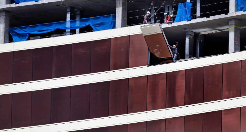 Construction workers install glass panels on the facade at the Wynn Resorts casino site in Everett, Mass., Thursday, April 26, 2018. Massachusetts gam...