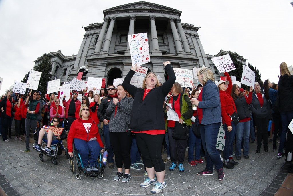 In this image taken with a fisheye lens, Stephanie Rolf, center, a teacher in the Douglas County, Colo., school system, leads a cheer during a teacher...
